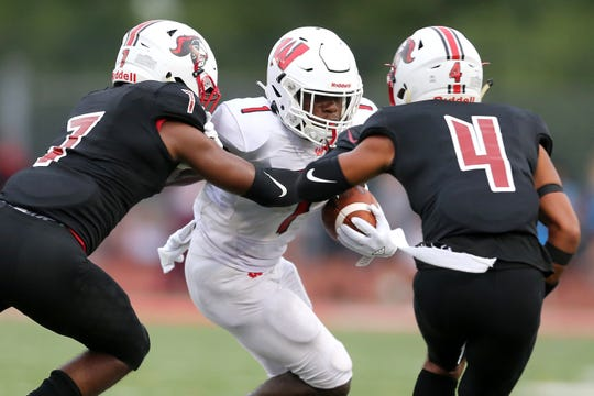 Lakota West running back David Afari (1) carries the ball as La Salle defensive backs Jaylen Johnson (7) and Iesa Jarmon (4) make the tackle in the first half of their football game, Friday, Aug. 30, 2019.