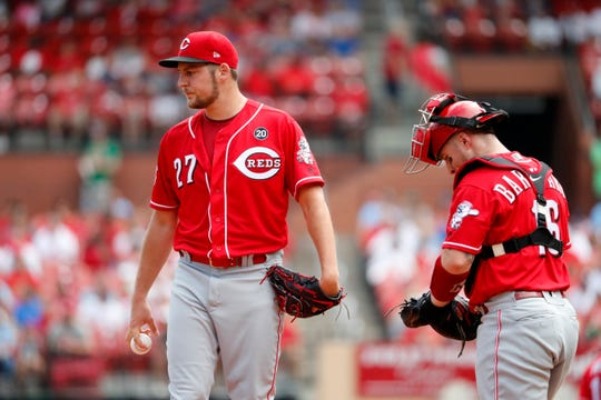 Cincinnati Reds starting pitcher Trevor Bauer, left, stands on the mound as catcher Tucker Barnhart comes out to talk after an RBI double by St. Louis Cardinals' Yadier Molina.