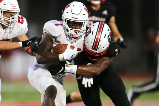 Lakota West running back David Afari (1) is tackled by La Salle defensive back Jaylen Johnson (7) in the first half Friday, Aug. 30, 2019.