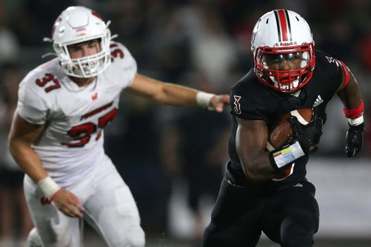 La Salle running back Gi'Bran Payne (3) carries the ball as Lakota West's Isaac Kolosik (37) gives chase in the second half of their game, Friday, Aug. 30, 2019.