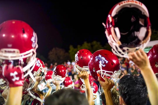 Montgomery Central players raise their helmets while getting together after the game concludes during a TSSAA football game between Montgomery Central Indians and West Creek Coyotes at Montgomery Central High School in Cunningham, Tenn., on Friday, Aug. 30, 2019.