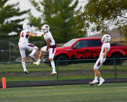 Ankeny's Brody Brecht (11) celebrates a touchdown with teammates on Friday, Aug. 30, 2019 during the season opening game between the Ankeny Hawks and the Ankeny Centennial Jaguars.