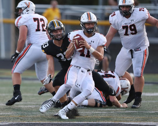 August 30, 2019; Pleasant Hill, IA, USA; West Des Moines Valley Tigers QB Braeden Katcher slips the tackle from Dominic Caggiano at Southeast Polk High School.