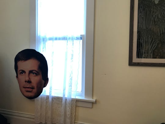 An outsized cutout of Democratic presidential candidate Pete Buttigieg's face leans against a window as field staffers nearby lead an organizing event on Thursday, Aug. 29, 2019, in Iowa City.