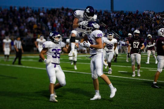 Waukee's Sam O'Dell (16), center, takes a celebratory leap after catching a pass on Aug. 30 at Valley Stadium.