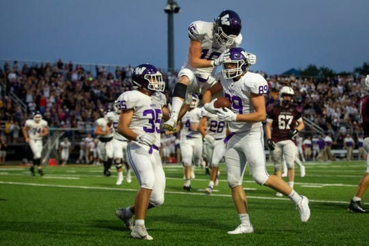 Waukee's Sam O'Dell (16) jumps onto Waukee's Edward Saidat Jr. (89) after he caught a pass for a touchdown to make the score 17-14 during their season opening game at Valley Stadium on Friday, Aug. 30, 2019 in West Des Moines. Waukee takes a 17-14 lead into halftime.