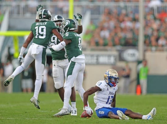 Michigan State Spartans' Josh Butler celebrates a tackle with teammates on Tulsa Golden Hurricane's Josh Johnson, Friday, August 30, 2019 at Spartan Stadium.