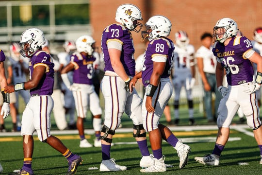 Warren De La Salle offensive line Grant Toutant (73) talks to teammate Derrelle Murray (89) during the Prep Kickoff Class against Muskegon, Aug. 30, 2019.
