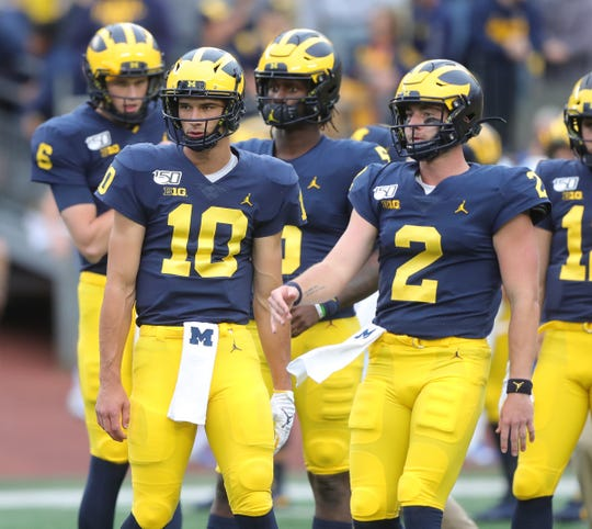 Michigan Wolverines quarterbacks Dylan McCaffrey (10) and Shea Patterson (2) warm up before action against the Middle Tennessee State Blue Raiders, Saturday, August 31, 2019 at Michigan Stadium.