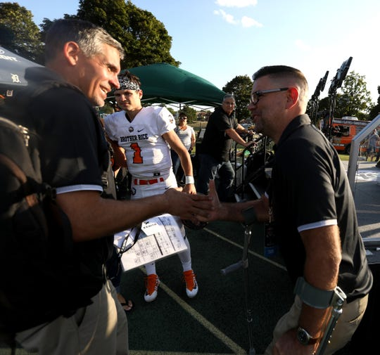 Birmingham Brother Rice head coach Adam Korzeniewski, left, and defensive coach Greg Piscopink congratulate each other after the 7-0 victory over Utica Eisenhower at Wayne State University on Thursday, August 29, 2019.