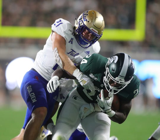 Michigan State Spartans' Elijah Collins is tackled by Tulsa Golden Hurricane's Bryson Powers, Friday, August 30, 2019 at Spartan Stadium.