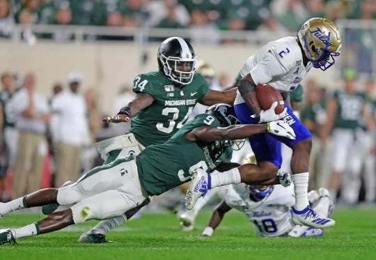 Michigan State Spartans' Dominique Long (9) tackles Tulsa Golden Hurricane's Keylon Stokes as Antjuan Simmons (34) pursues Friday, August, 30, 2019 at Spartan Stadium.