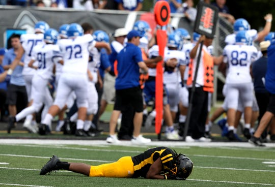 As Novi Detroit Catholic Central celebrates on the sidelines, Detroit King's Marshawn Lee reacts after CC came up with the football at Wayne State University on Aug. 31, 2019. Catholic Central won the game 24-22.