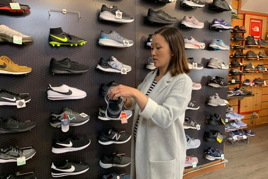 In this photo taken Wednesday, Aug. 28, 2019, Jennifer Lee, whose family owns Footprint shoe store in San Francisco, stands by a wall of athletic shoes, many of which are made in China and will be subject to new U.S. tariffs on Chinese goods starting Sept 1.