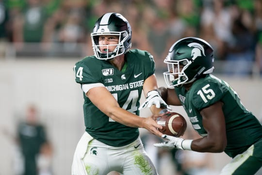 Michigan State quarterback Brian Lewerke hands the ball off to running back La'Darius Jefferson in the third quarter.