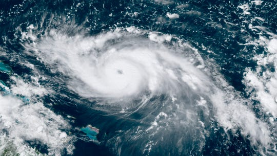 This GOES-16 satellite image taken Friday, Aug. 30, 2019, at 17:30 UTC and provided by National Oceanic and Atmospheric Administration (NOAA), shows Hurricane Dorian, right, moving over open waters in the Atlantic Ocean. Forecasters are now saying Dorian could be a Category 4 with winds of nearly 140 mph when it is forecasted to hit Florida late Monday or early Tuesday. It's also imperiling the Bahamas, where the storm is expected to hit by Sunday.