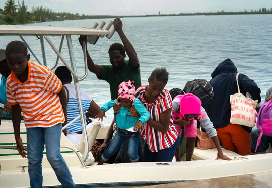 A woman carries a girl in her arms after being evacuated from a nearby Cay due to the danger of floods after arrive on a ship at the port before the arrival of Hurricane Dorian in Sweeting's Cay, Grand Bahama, Bahamas, Saturday Aug. 31, 2019.   Dorian bore down on the Bahamas as a fierce Category 4 storm Saturday, with new projections showing it curving upward enough to potentially spare Florida a direct hit but still threatening parts of the Southeast U.S. with powerful winds and rising ocean water that causes what can be deadly flooding.  (AP Photo/Ramon Espinosa)