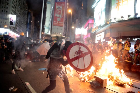 A protestor uses a shield to cover himself as he faces policemen in Hong Kong, Saturday.