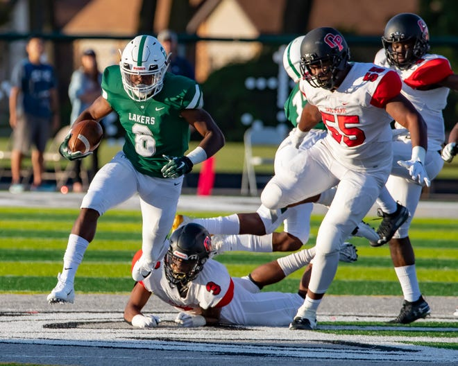 West Bloomfield running back Donovan Edwards (6) runs past Oak Park defenders during Friday's game.