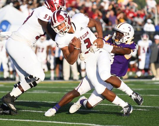 De La Salle's Galiko Lovelace (3) tackles Muskegon quarterback Cameron Martinez (13) in the first half.