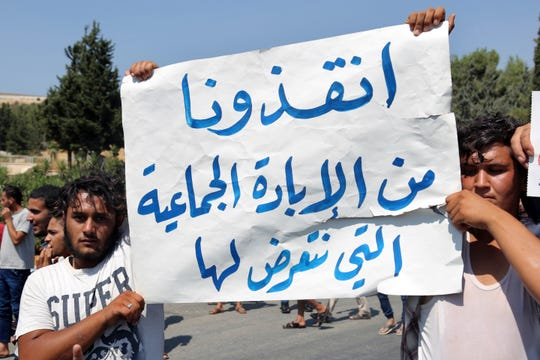 "Protesters hold a placard with Arabic that reads ""Save us from this genocide we are subjected to,"" during a demonstration at the Bab al-Hawa border crossing with Turkey, Syria, Friday, Aug. 30, 2019, demanding that Ankara either open the border or end attacks by the government. Opposition activists said Turkish borders guards fired tear gas at the protesters."