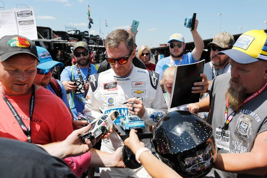 Dale Earnhardt Jr signs autographs before qualifying for the NASCAR Xfinity Series race at Darlington Raceway on Saturday.
