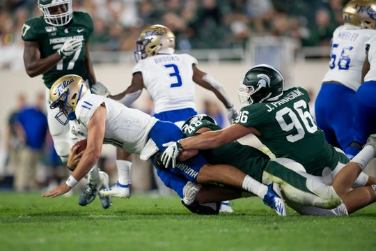 Tulsa quarterback Zach Smith, left, is sacked by Michigan State defensive end Kenny Willekes and defensive end Jacub Panasiuk in the fourth quarter.