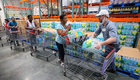 "A shopper is grateful to get two cases of bottled water ""the limit per customer"" at a Costco store in Altamonte Springs, Fla., Friday, Aug. 30, 2019, as central Florida residents prepare for a possible strike by Hurricane Dorian."