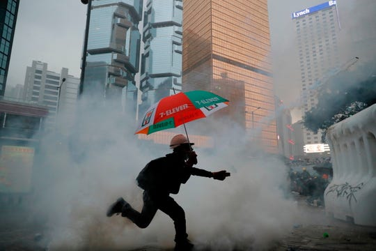 A protester throws back an exploded tear gas shell at police officers in Hong Kong, Saturday.