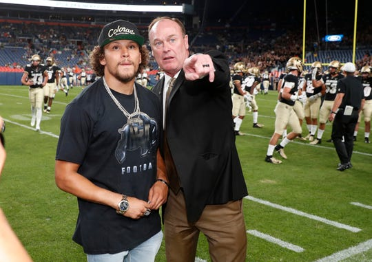 Denver Broncos running back Phillip Lindsay, left, who played his collegiate football at Colorado, confers with Rick George, athletic director of Colorado, as Lindsay looks on during warmups before Colorado faces Colorado State in an NCAA college football game Friday, Aug. 30, 2019, in Denver. (AP Photo/David Zalubowski)