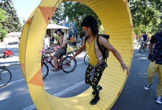 John Paul walks in the human hamster wheel during the Tour de Fat bike parade in downtown Fort Collins, Colo. on Saturday, Aug. 31, 2019.