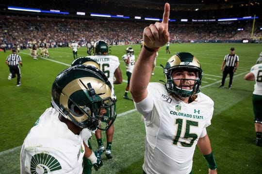 Colorado State University junior quarterback Collin Hill (15) points to the crowd while celebrating a touchdown pass to junior recover Warren Jackson (9) during the Rocky Mountain Showdown rivalry football game against the University of Colorado on Friday, August 30, 2019, at Broncos Stadium at Mile High in Denver, Colo.