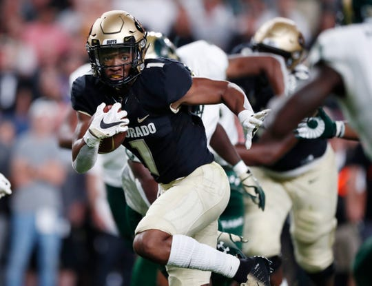 Colorado running back Jaren Mangham, left, drives for a short gain as Colorado State cornerback Anthony Hawkins comes in for the stop in the first quarter of an NCAA college football game Friday, Aug. 30, 2019, in Denver. (AP Photo/David Zalubowski)