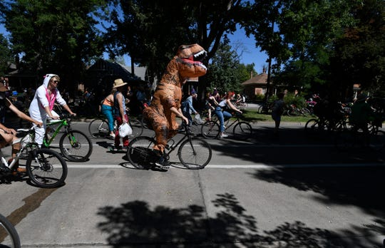 A person dressed as a dinosaur bikes during the Tour de Fat bike parade in downtown Fort Collins, Colo. on Saturday, Aug. 31, 2019.