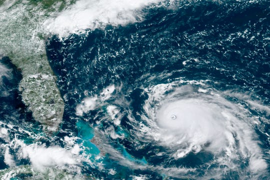 This GOES-16 satellite image taken Saturday, Aug. 31, 2019, at 16:00 UTC and provided by National Oceanic and Atmospheric Administration (NOAA), shows Hurricane Dorian, right, churning over the Atlantic Ocean. Hurricane Dorian bore down on the Bahamas as a fierce Category 4 storm Saturday, with new projections showing it curving upward enough to potentially spare Florida a direct hit but still threatening parts of the Southeast U.S. with powerful winds and rising ocean water that causes what can be deadly flooding.(NOAA via AP)