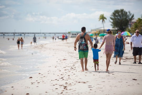 Visitors to Fort Myers Beach walk near the Lani Kai Island Resort on Saturday, Aug. 31, 2019.