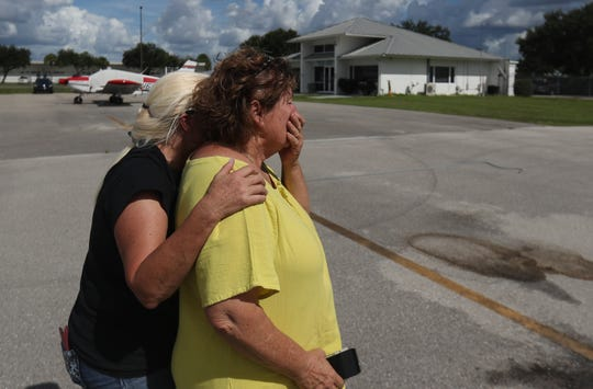 Kathy Irey and Laura Smith, both volunteers for Clewiston Amimal Control react after loading shelter dogs into a Pilots N Paws airplane at the Immokalee Airport for transfer to Big Fluffy Rescue in Nashville. The dogs was one of several in danger of being euthanized unless transferred away from Hurricane Dorian's path.