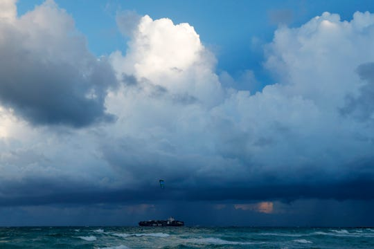 A container ship heads out to sea into bands of rain as a kitesurfer enjoys the winds off South Beach, Friday, Aug. 30, 2019, on Miami Beach, Fla. All of Florida is under a state of emergency and authorities are urging residents to stockpile a week's worth of food and supplies as Hurricane Dorian gathers strength and aims to slam the state as soon as Monday as a Category 4 storm.