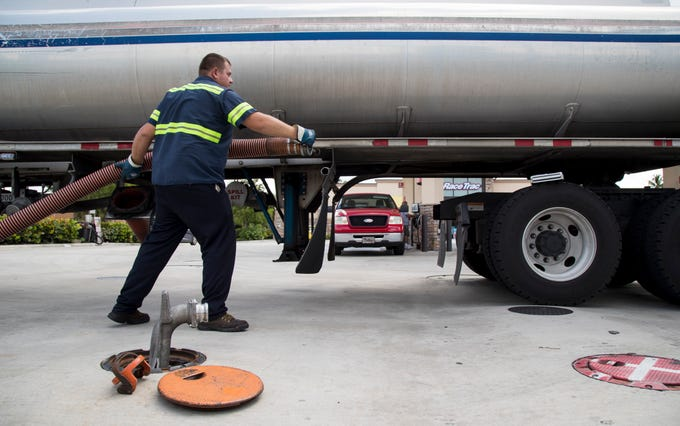 Alex Boskovski of Tampa finishes filling the gas tanks with fuel at the RaceTrac gas station at the corner of Cleveland Avenue and Edison Avenue on Saturday, August 31, 2019, in Fort Myers as cars and trucks pull up to the pumps to refuel.