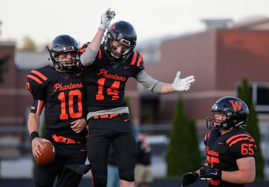 West De Pere's Josh Blount (10) celebrates after scoring a touchdown with teammate Marcus Van Vreede (14) in a win over New London this season.