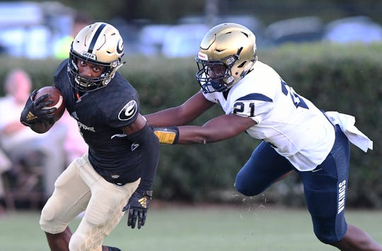 Greer's Cameron Martin (4) can't escape Spartanburg's Paris Ferguson (21) Friday, August 30, 2019, at Greer's Dooley Field.