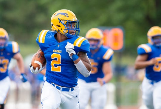 Carmel High School senior Dylan Downing (2) rushes the ball out of the backfield, running for a long touchdown run, during the first half of action. Carmel High School hosted Noblesville High School in IHSAA varsity football action Friday, Aug. 30, 2019.