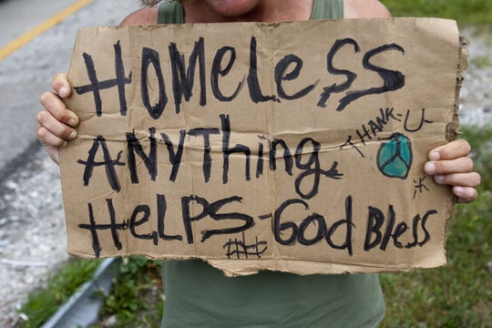 Encarnacion Owenby, 35, holds the sign seeking donations at an offramp of Keystone Avenue, southbound, at 86th Street, Indianapolis, IN, Thursday, July 29, 2009.  This spot is considered prime real estate for panhandlers.