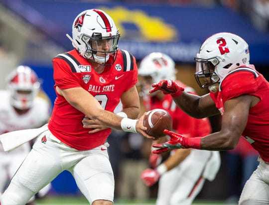 Ball State Cardinals quarterback Drew Plitt (9) hands the ball off to running back Caleb Huntley (2) during the first half of action in the Kickoff Classic. Indiana University faced off against Ball State at Lucas Oil Stadium in Indianapolis, Saturday, Aug. 31, 2019.