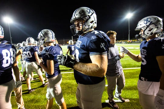 Cedar Rapids Xavier's Josh Volk (73) bumps fists with teammates after a week one varsity high school football game, Friday, Aug. 30, 2019, at Saints Field in Cedar Rapids, Iowa.