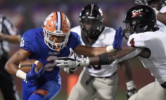 Madison Central's Duke Arnold (2) stiff arms Brandon's Willie Miller (4) at Madison Central High School on Friday, August 30, 2019, in Madison, Miss.