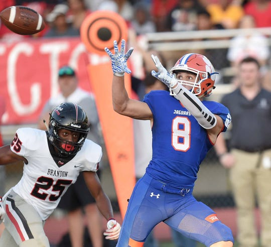 Madison Central's Logan Reed (8) catches a touchdown pass over the middle against Brandon's Richard O'Bryant (25) at Madison Central High School on Friday, August 30, 2019, in Madison, Miss.