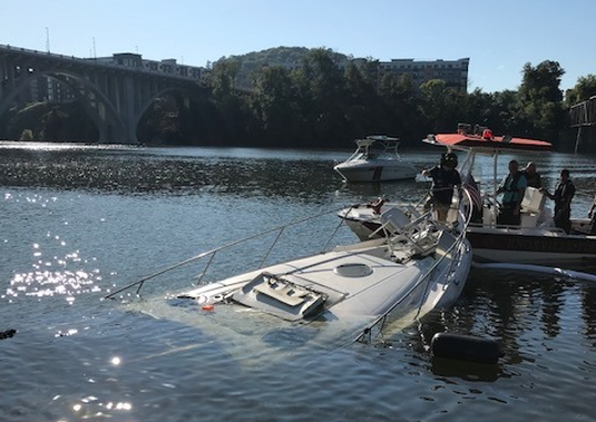 Crews work to recover a boat that burned and sank into the Tennessee River on Aug. 31, 2019.
