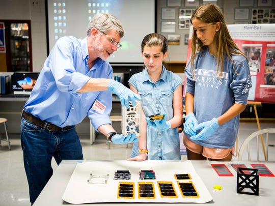 Peter Thornton, research and development scientist in ORNL's environmental science division, explains to students Sophie Sluss, center, and Kate Laffoon, right, how different components of the cube satellite stack together at Robertsville Middle School in Oak Ridge on Wednesday, August 28, 2019.