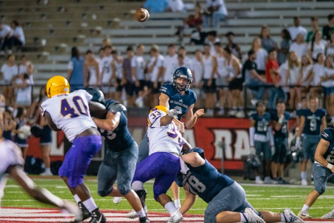 STM's quarterback Caleb Holstein throws a pass to a receiver as the St. Martinville Tigers take on the St. Thomas More Cougars at Cajun Field during the Kiwanis Club Football Jamboree on August 30, 2019.